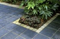 Slate paving, edging of granite setts, Fatsia japonica, heuchera