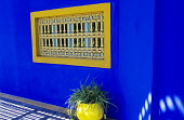Blue painted wall, yellow container