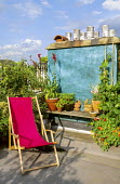Roof terrace, pink deckchair, painted green wall, containers, chimney pots