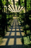 Stone pergola, pattern of light and shade, view to bench