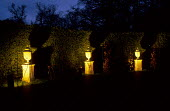 Reconstituted stone urns lit by spike spotlights hidden by green-painted tin cowls