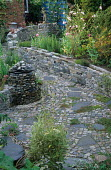 Town garden with cobbles, stone wall, stone cairn, lavatera