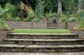 Town garden, steps to lawn, brick raised beds and terrace, play area with slide and cabin