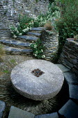 Sheltered stone seating area with millstone table