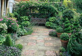 Brick and stone terrace with rose arbour