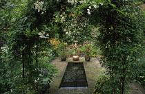 Town garden, pond, Solanum jasminoides on arch, herringbone pattern brick surface