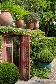 Red gate into walled garden, box balls in containers