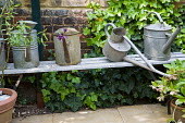Metal watering cans on bench