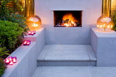 Outdoor fireplace, tealights on raised bed wall