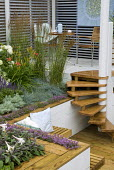 Steps to raised patio from sunken terrace, wooden seating with thyme rill, hemerocallis