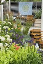 Steps up to raised terrace, hylotelephium syn. sedum, agapanthus, hydrangea, hemerocallis, grasses, artwork