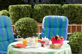 Table and chairs on terrace screened by clipped box in containers
