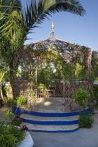 Indian wrought-iron pavilion, blue steps, bougainvillea