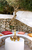 Built-in bench with cushions, dry-stone wall, cups and bottle, olive tree