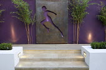 Metal panel with cut-out figure, purple painted wall, Phyllostachys aureosulcata 'Aureocaulis'