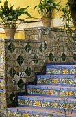 Mosaic tiled stairs, yellow wall, containers