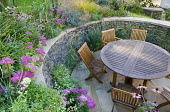 Circular seating area, retaining dry-stone wall, table and chairs