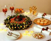 Table, Christmas pudding wreath, mince pies, napkins with rosemary rings, champagne flutes, fruit