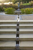 Rill from circular pond down steps, sculpture as focal point