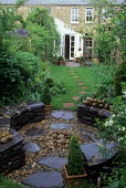 Circular stone seating enclosure with bubble fountain, stepping stone path
