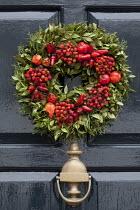 Berry and chilli pepper door wreath on black front door