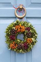 Christmas door wreath with berries and pine cones