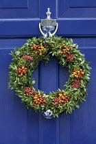 Blue front door with Christmas berry wreath