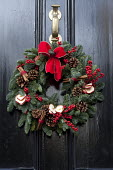 Christmas wreath with berries, pine cones, cinnamon and bow on black front door