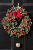 Christmas wreath with holly berries on black front door