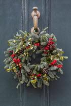 Christmas door wreath with berries, mistletoe and pine cones