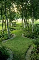 Serpentine grass path under trees, moving strip