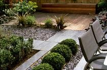 Black paving, slate chippings mulch, decking, box balls, astelia, timber bench