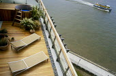 Roof terrace with steamer chairs and hot tub, view over Thames with boat, London Docklands