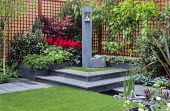 Red trellis, raised beds, slate paving, sculpture by Michael Dan Archer, Astilbe x arendsii 'Fanal'