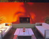 Contemporary table and chairs around fireplace, red painted wall