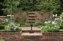 Herringbone brick patio, reclaimed brick wall, rill water feature, box cubes and white planting, aquilegias, alliums, geraniums and roses