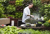Chef cooking in outdoor kitchen, living green salad wall
