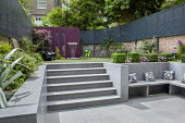 Steps leading to upper garden level, split-level garden, compressed Italian lava stone, green child's puppy chair by Magis