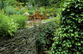 Dry-stone wall, ivy, stream, table and chairs