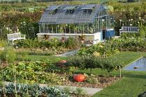 Overview of vegetable garden with greenhouse, pumpkins