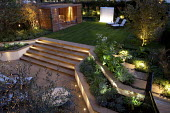 Overview of lit town garden, timber pavilion, York stone patio and steps