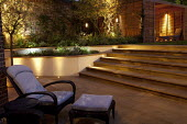 Recliner on contemporary York stone patio at night, lighting