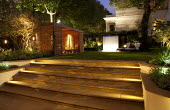 Contemporary garden at night, York stone steps, timber pavilion, lit stainless steel wall water feature, chairs on lawn
