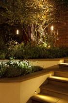 Electric lanterns in tree, raised beds, steps, uplit amelanchier