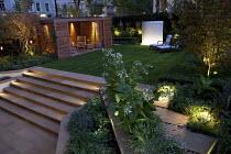 Overview of lit town garden, lavender, Nicotiana sylvestris, York stone paving