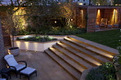Lit steps, patio with lounger, raised beds