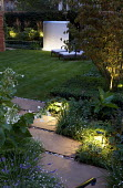 Lit stone path and lit wall water feature, recliner chairs on lawn, Nicotiana sylvestris, York stone paving