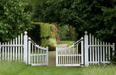 Curved white picket gate, view to garden with roses, driveway