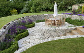 Sunken garden, curved flint stone walls around crazy paving patio with table, chairs and umbrella, Salvia nemorosa 'Caradonna' and low clipped box hedging