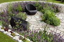 Contemporary chairs on sunken patio enclosed by curved flint stone walls, Salvia verticillata 'Purple Rain', Alchemilla fulgens, sempervivums